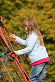 Climbing. Blonde young girl climbing on an adventure playground stock image