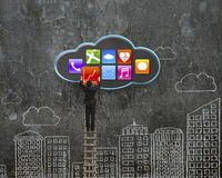 Climbing businessman get app icon from black cloud Royalty Free Stock Images
