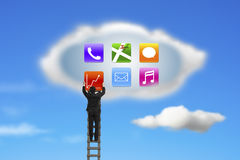 Climbing businessman getting app icons from cloud with nature sk Stock Photos