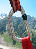 Climbing carabiner closup on the mountains background. Stock Photo