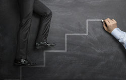 Climbing the career steps. Businessman climbing the career steps drawn on a black chalkboard stock images