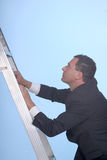 Climbing the corporate ladder. Business man climbing the corporate ladder stock photography