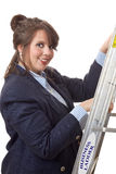 Climbing the corporate ladder; isolated. Young business woman climbing a ladder; business metaphor for climbing the business ladder; isolated on a white Royalty Free Stock Image