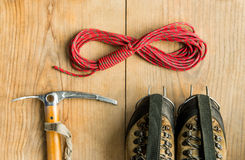 Climbing equipment: rope, trekking shoes, ice tools, ice ax, crampons on wooden background, top view Royalty Free Stock Image