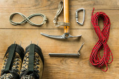 Climbing equipment: rope, trekking shoes, ice tools, ice ax, ice screws, crampons, carbine on wooden background, top view Royalty Free Stock Images