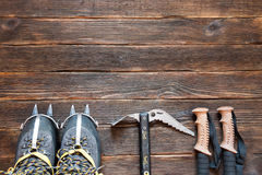 Climbing equipment: trekking shoes, crampons, ice tools, ice ax,. Ice screws, trekking poles on dark wooden background, top view. Travel concept Royalty Free Stock Images