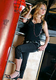 Climbing fashion. Young beautiful woman in trendy outfit, standing on ledder Stock Photography