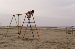 Climbing frame. Young girl playing on a climbing pole - looking down royalty free stock image