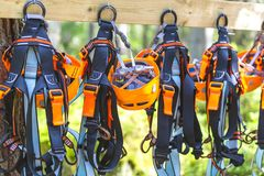 Free Climbing Gear Equipment - Orange Helmet Harness Zip Line Safety Equipment Hanging On A Board. Tourist Summer Time Adventure Park Royalty Free Stock Images - 100945489