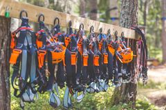 Climbing gear equipment - orange helmet harness zip line safety equipment hanging on a board. Tourist summer time adventure park. Family and company team royalty free stock photos