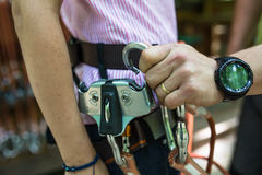Climbing gear. Man securing professional climbing gear to a woman's belt Stock Image