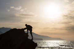 Climbing hiking silhouette in mountains and ocean Royalty Free Stock Images