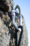 Climbing iron. With carabiner and rope on rock Stock Images