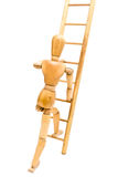 Climbing Ladder. Wooden artist's drawing mannequin climbing up a ladder symbolizing many concepts such as climbing, home improvement, construction equipment Royalty Free Stock Photo