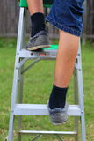 Climbing the Ladder. A close up view of someone climbing up a ladder Stock Photos