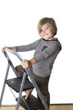 Climbing the ladder. Young boy wearing striped shirt and hood, standing on a ladder, smiling at the camera Stock Image