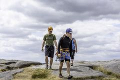 Climbing learners following their climbing instructor in rough t stock image