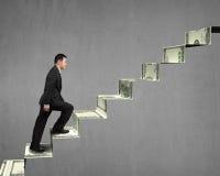 Climbing on money stairs. Concrete background Stock Photos