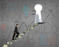 Climbing on money stairs with business concept doodles on wall. Climbing on money stairs with business concept doodles on concrete wall Stock Images