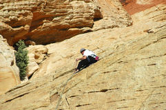 Climbing the Mountain. A guy checking his ropes while climbing a mountain Stock Photo
