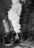 Climbing the Mountain. Vintage steam locomotive pulls a heavy load up a mountain stock image