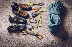 Climbing and mountaineering equipment on a carpet. Shoes, carbine, rope, lope, ascend-er. Concept of outdoor and extreme sport. Royalty Free Stock Image