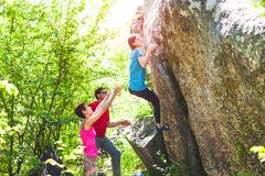 Climbing in nature. Friends climb to the stone. The girl climbs on the stone, and friends support her. Bouldering in nature. stock photography