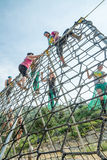 Climbing the obstacle couse. BOISE, IDAHO/USA - AUGUST 8, 2014: Runners working on getting over the rope obstacle during the Dirty Dash in Boise, Idaho Stock Photo