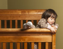 Climbing out of the crib. Toddler climbing out of her crib Stock Photography