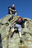 Climbing people. One friend is waiting of next one Stock Photography