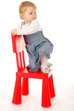 Climbing on red chair little girl Stock Image