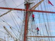 Climbing the rigging. Two crew members climbing the 9 miles of rigging of a tall ship Royalty Free Stock Images