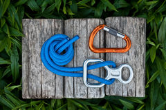 Climbing rope with a descender and a carabiner. Climbing descender with a climbing rope and a carabiner on a natural background royalty free stock images