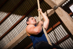 Climbing a rope at a gym Royalty Free Stock Image