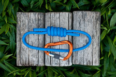 Climbing rope on a natural background. Joined rope ends with double overhand knots and a carabiner on a natural background Stock Images