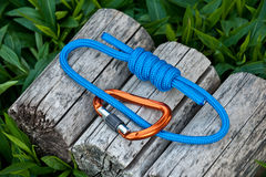 Climbing rope on a natural background. Joined rope ends with double overhand knots and a carabiner on a natural background Royalty Free Stock Photo