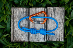 Climbing rope on a natural background. Joined rope ends with double overhand knots and a carabiner Stock Photo