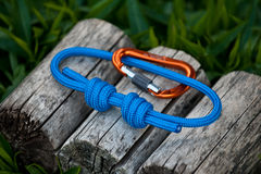 Climbing rope on a natural background. Joined rope ends with double overhand knots and a carabiner Royalty Free Stock Images