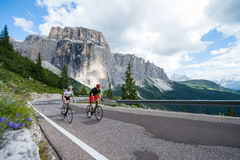 Climbing route on cycle race-dolomites-italy. Assistant in the bike race- a men helps a woman Royalty Free Stock Photo