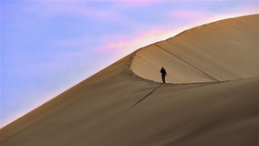 Climbing the Sand Dune. With a huge sand dune wind blows the sand. The slope of the dune moves slowly traveler