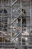 Climbing Scaffold Steps_7940-1S. Construction Worker Climbing Up Scaffold Steps Royalty Free Stock Photo