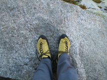 Climbing shoes. Yellow climbing shoes on grey rock stock image