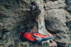 Climbing shoes on rock. Red climbing shoes on stone rock otdoor Royalty Free Stock Image