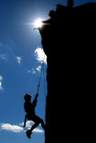 Climbing silhouette. Silhouette of boy rappelling down a cliff Royalty Free Stock Image