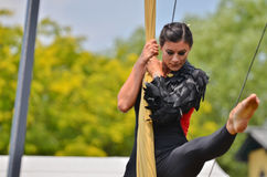Climbing the Silks. An aerial performer climbs the silks as she extends her legs into the splits during an outdoor performance Royalty Free Stock Images