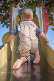 Climbing The Slide Stock Photo