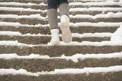 Climbing snow covered stairs to Yamadera shrine. Person climbing snow covered stairs (only showing boots, socks  and legs) to visit the beautiful Yamadera Stock Photo