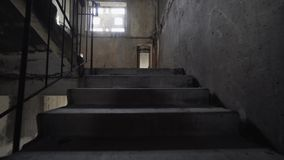 Climbing spooky stairs in darkness. Going up dark and dangerous stairs in creepy stairwell alone. slow motion