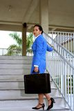 Climbing Stairs. Businesswoman walking up stairs carrying a briefcase Stock Photo
