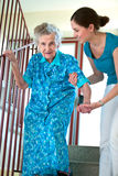 Climbing stairs with caregiver. Senior women is climbing stairs with caregiver Stock Images